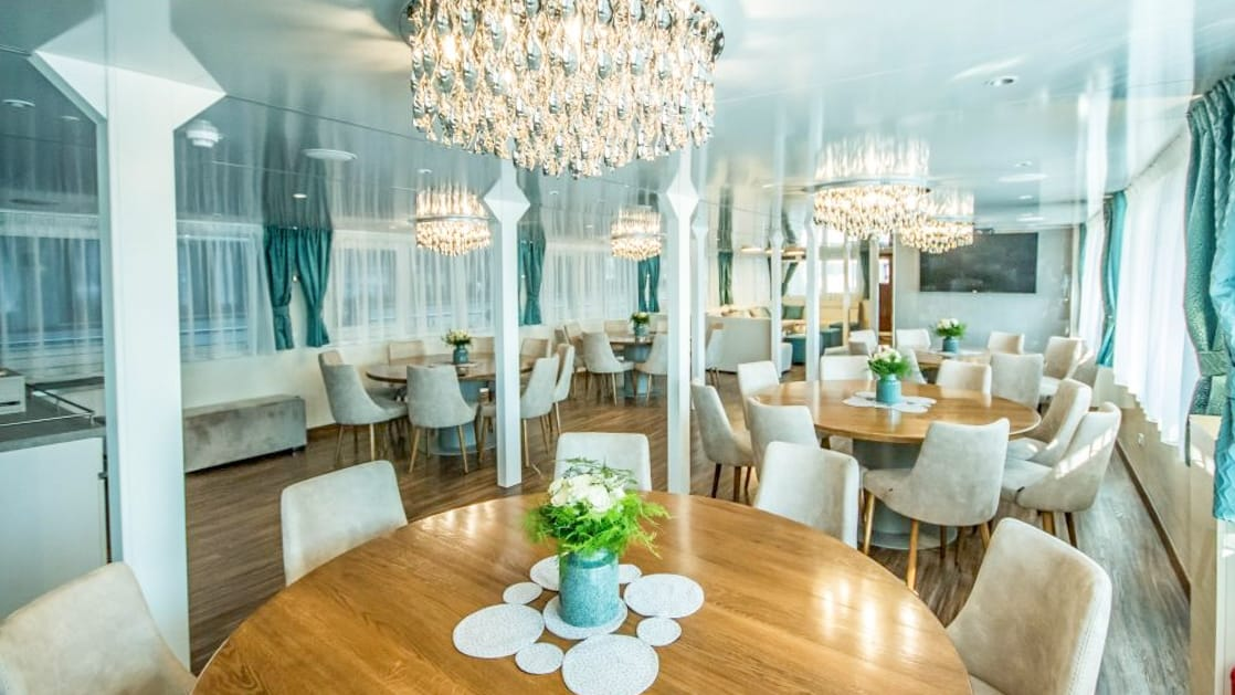 Markan Dining Room with round tables, chairs, large windows and chandeliers.