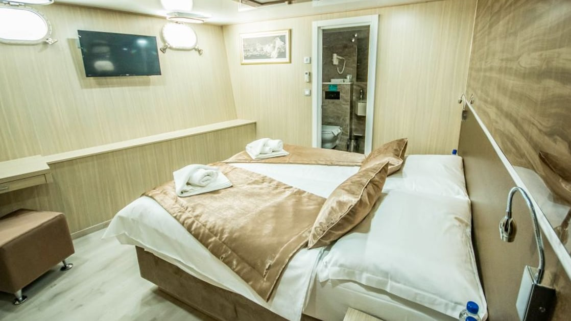 Markan Lower Deck cabin double bed, portholes, desk, bathroom and ottoman.