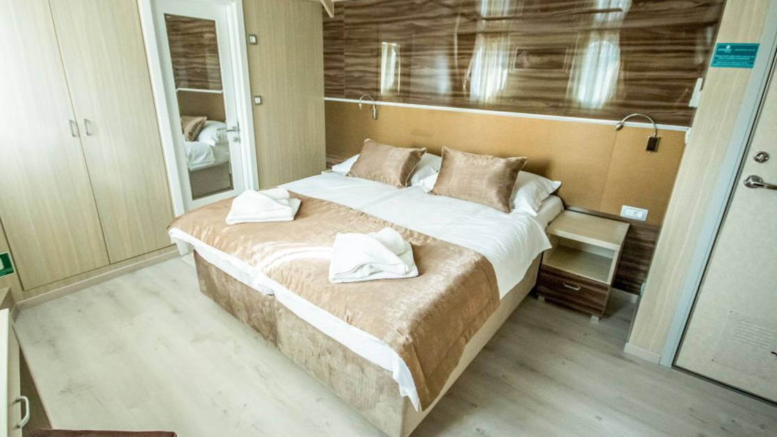 Markan Main Deck Cabin with double bed, bathroom, closet, nightstand, reading lights and small portholes.