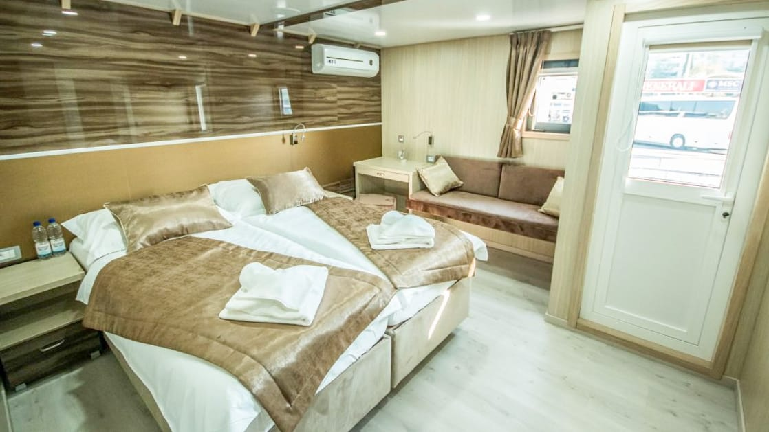 Markan VIP Upper Deck cabin with seating area, large double bed, door out to private balcony, nightstand and reading lights with large window.