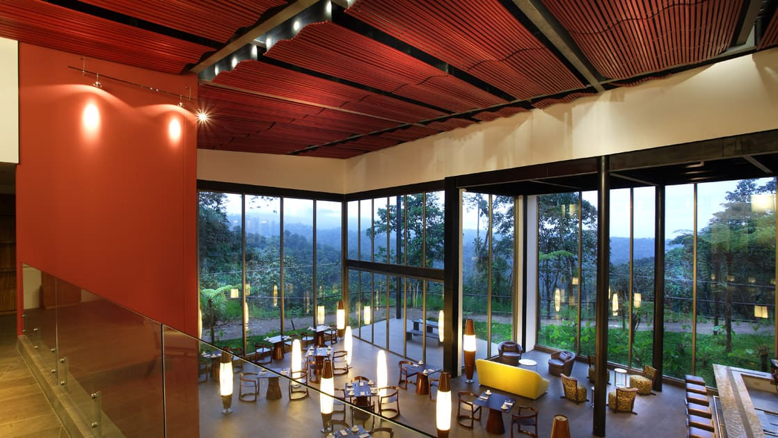 Lights reflect over the dining room and along the large windows that face the cloud forest at the Mashpi eco lodge, a family-friendly, luxury accommodation in Ecuador