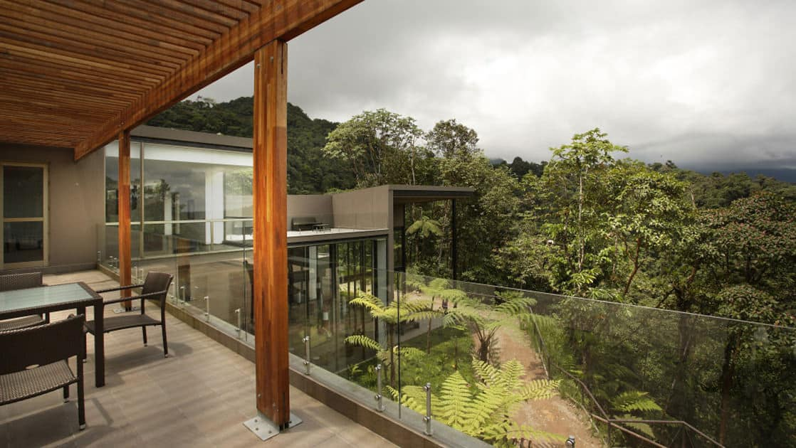 Tables and chairs on a patio overlooking the forest during a cloudy day at the Mashpi eco Lodge, near Quito, Ecuador