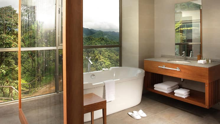 The Yaku Suite bathroom with a full tub, vanity, and large windows overlooking the jungle at the Mashpi eco lodge, a luxury wellness retreat in Ecuador