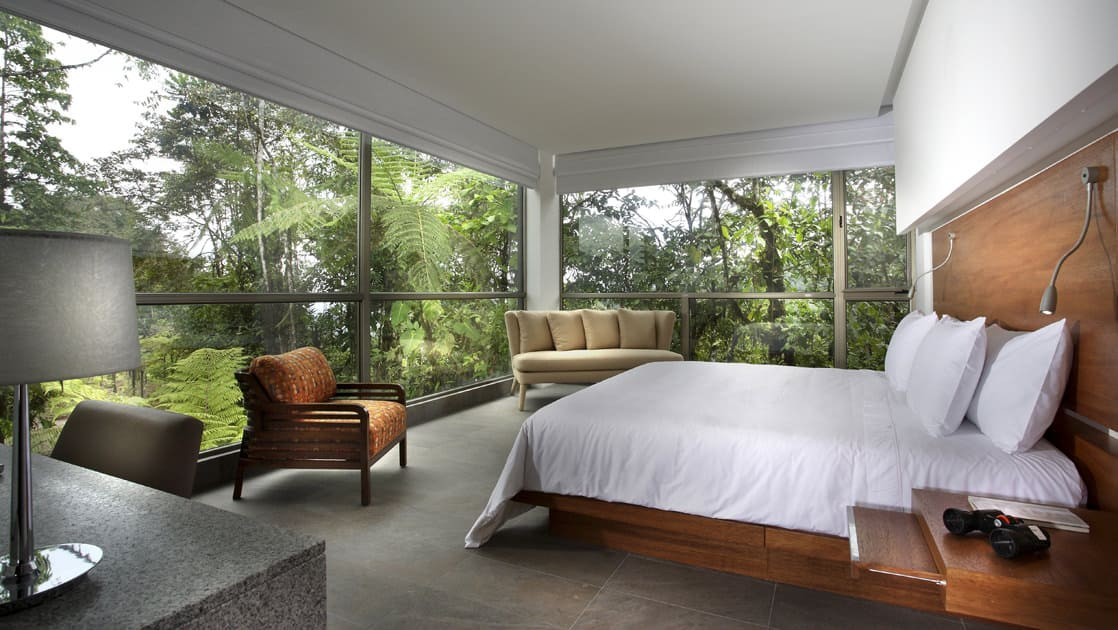 The Yaku King Suite has a large bed, fresh linens, and panoramic view of the jungle at the Mashpi eco lodge, a luxury wellness retreat in Ecuador