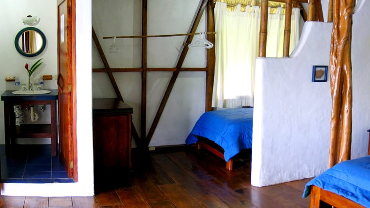 Inside the cabana with two beds and a partial dividing wall at the Napo Wildlife Center, a luxury eco-lodge near a rainforest reserve in the Ecuadorian Amazon