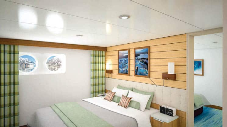 Large bed and two portholes in Category 2 cabin aboard National Geographic Quest luxury expedition ship