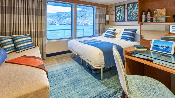 Queen bed, sofa, desk, chair and large windows in cabin aboard National Geographic Venture expedition ship