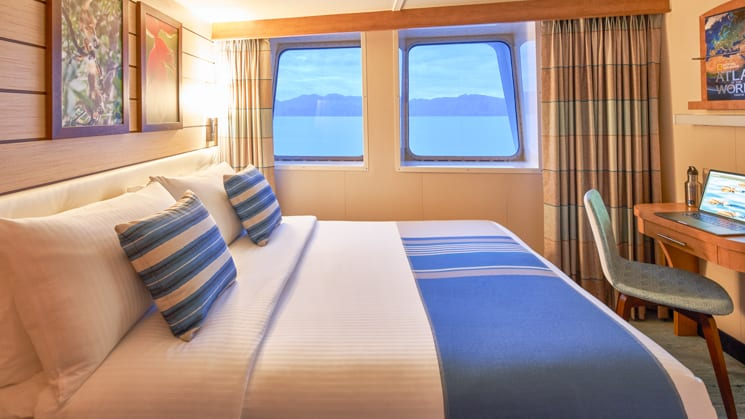 Queen bed, desk, chair and two large windows in cabin aboard National Geographic Venture expedition ship