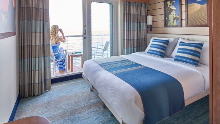 Woman sitting on private balcony of cabin with large bed aboard National Geographic Venture expedition ship