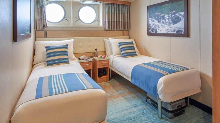 Cabin interior with two beds, nightstands, and two portholes aboard National Geographic Venture expedition ship