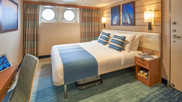 Cabin with large bed, nightstand, desk, chair and two portholes aboard National Geographic Venture expedition ship
