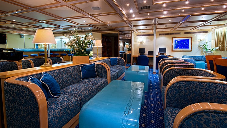Lounge area of Corinthian small ship in Mediterreanan with couches and tables.