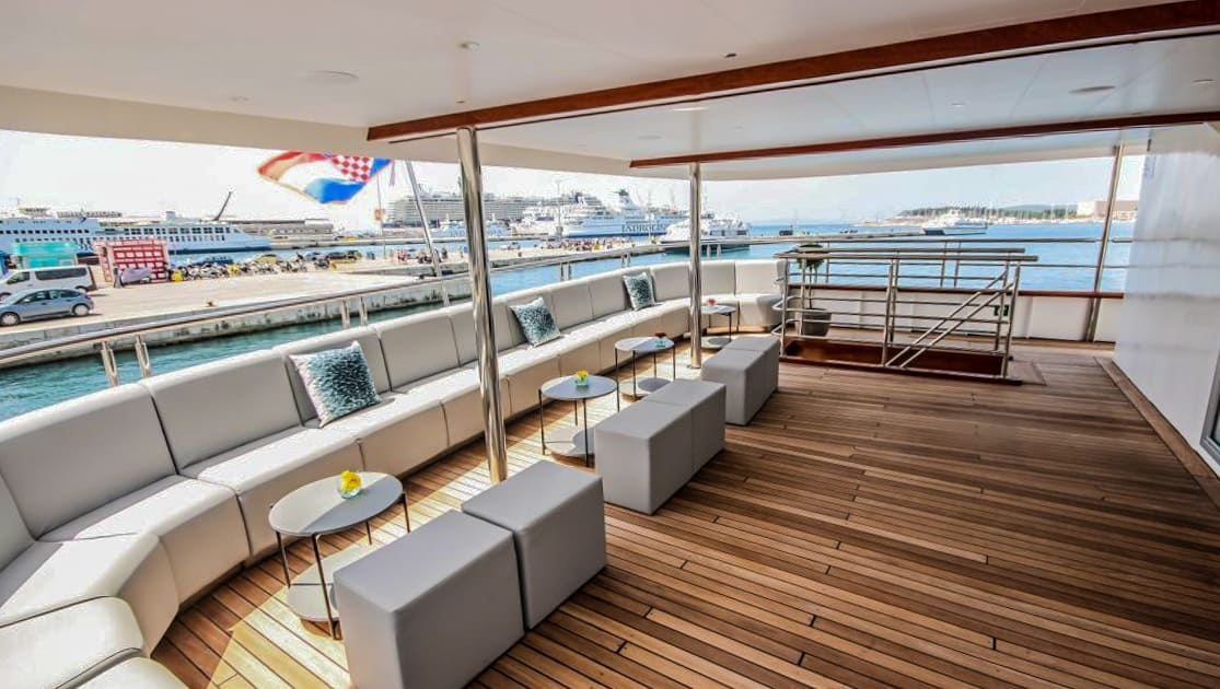 Main Deck aft al fresco seating area with long grey fabric wraparound couch, small round tables and square grey ottomans with teak decking Nautilus Croatia & Mediterranean deluxe small yacht.