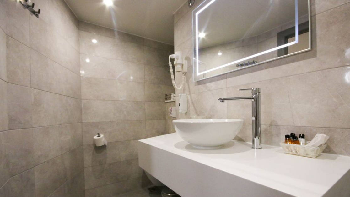 Cabin bathroom with light stone tile, white countertop and bowl sink, mounted hairdryer, toiletries and lighted rectangular mirror aboard Nautilus Croatia & Mediterranean deluxe small yacht.