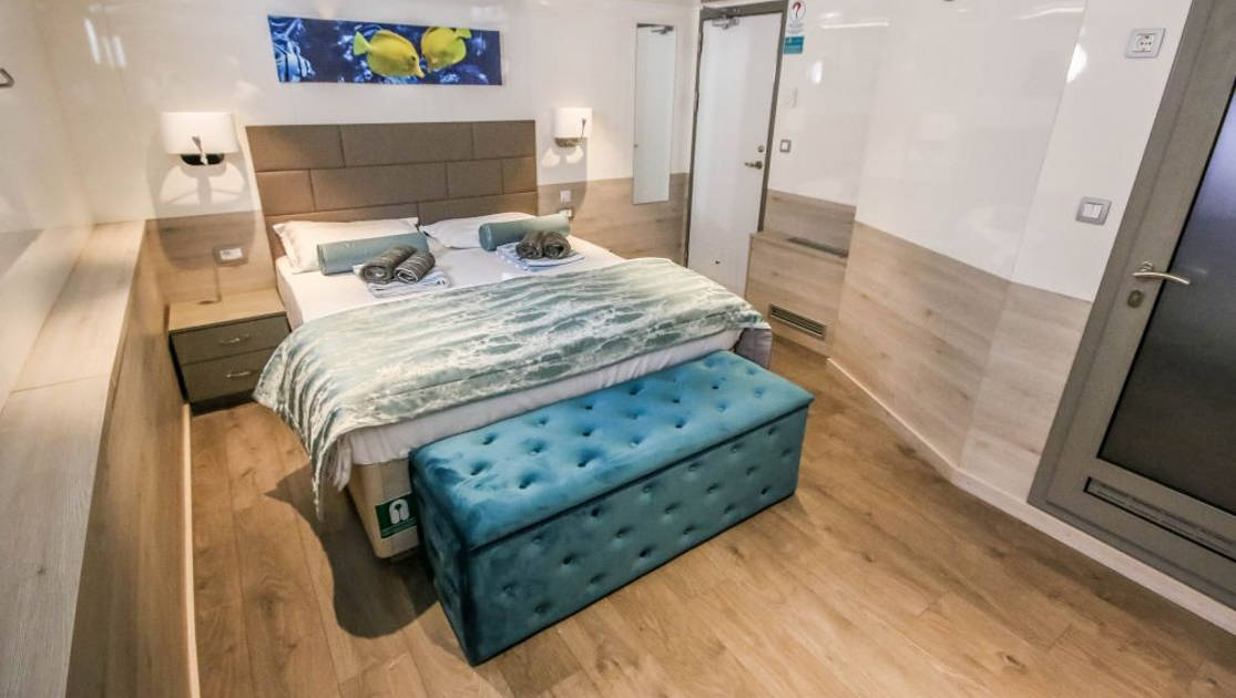 Guest cabin with double bed, plush bedding, blue velvet storage chest, wooden accents, shiny white walls and two bedside tables with lamps aboard Nautilus Croatia & Mediterranean deluxe small yacht.