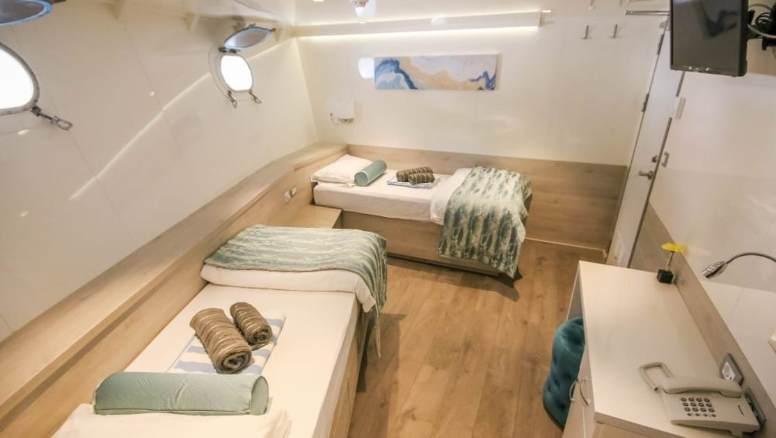 Cabin #13 with two fixed twin beds, two portholes, desk, phone, TV on wall and accents of white, wood and aqua aboard Nautilus Croatia & Mediterranean deluxe small yacht.