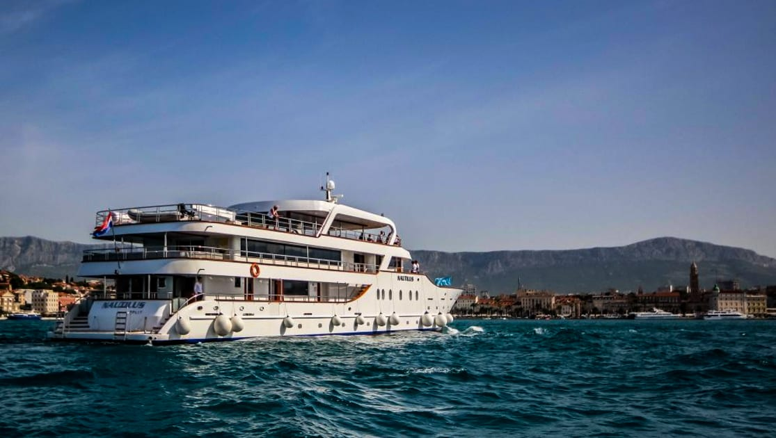 Exterior aft view of Nautilus Croatia & Mediterranean deluxe small yacht pulling into port on a sunny day.