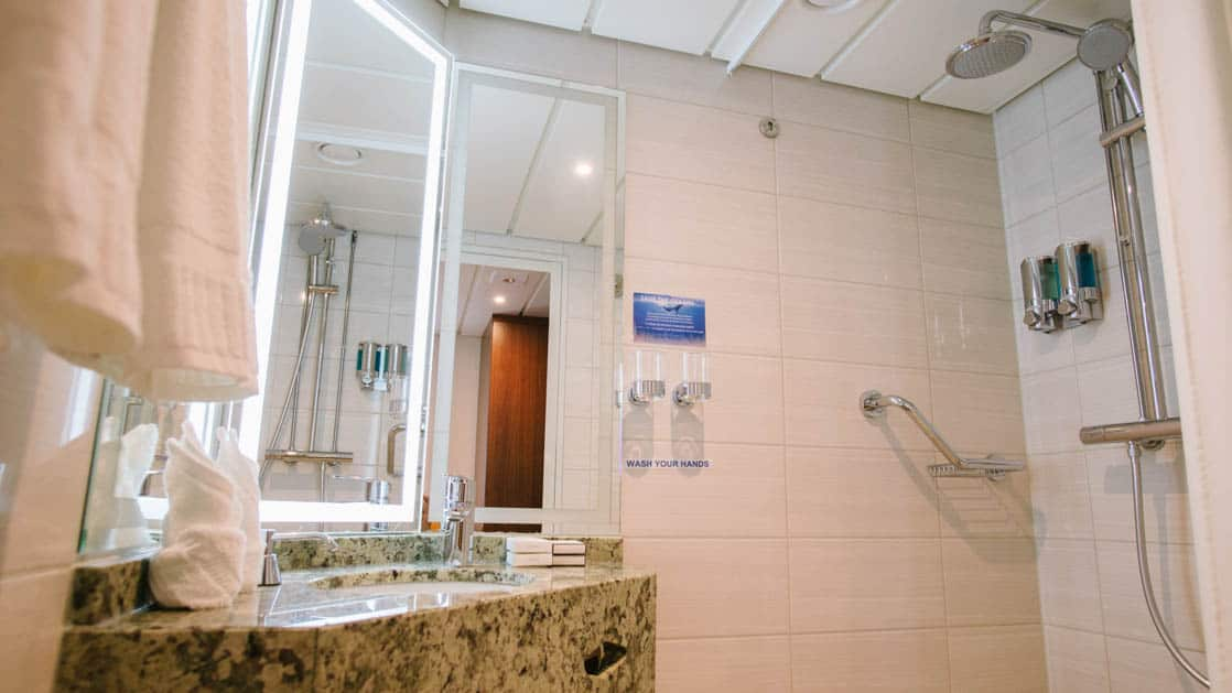 large bathroom with granite counter top and shower aboard Ocean Adventurer small ship