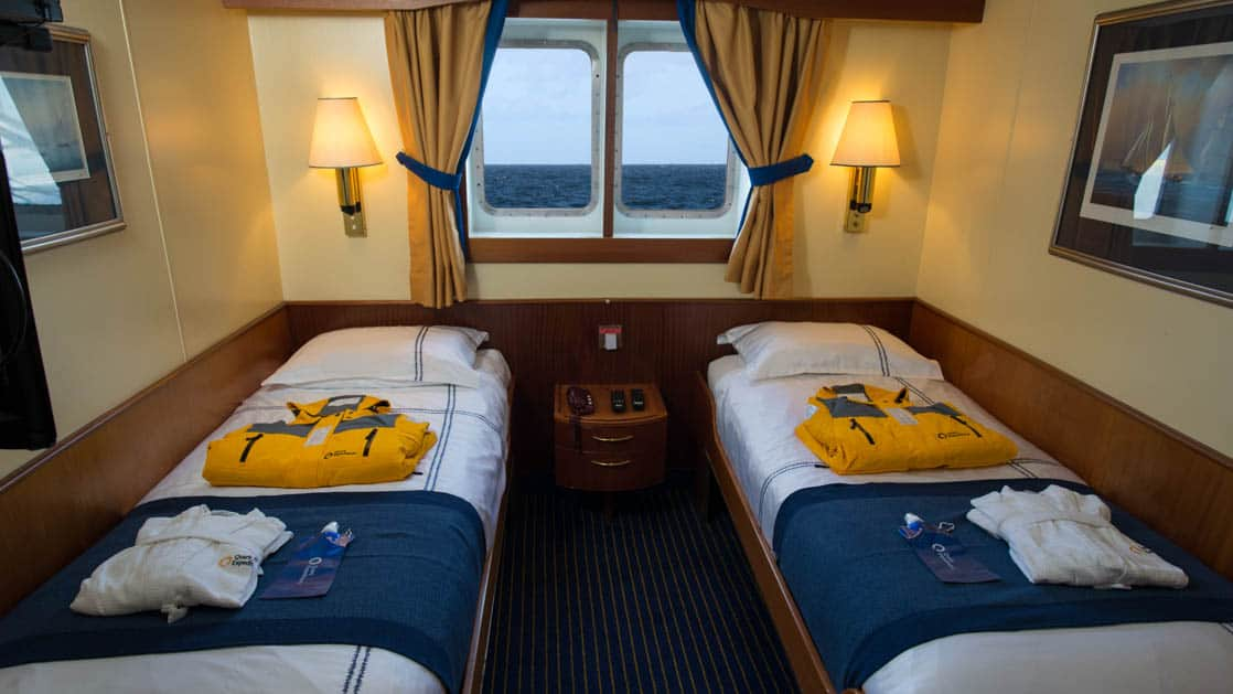 room with 2 twin beds and a window aboard the Ocean Adventurer