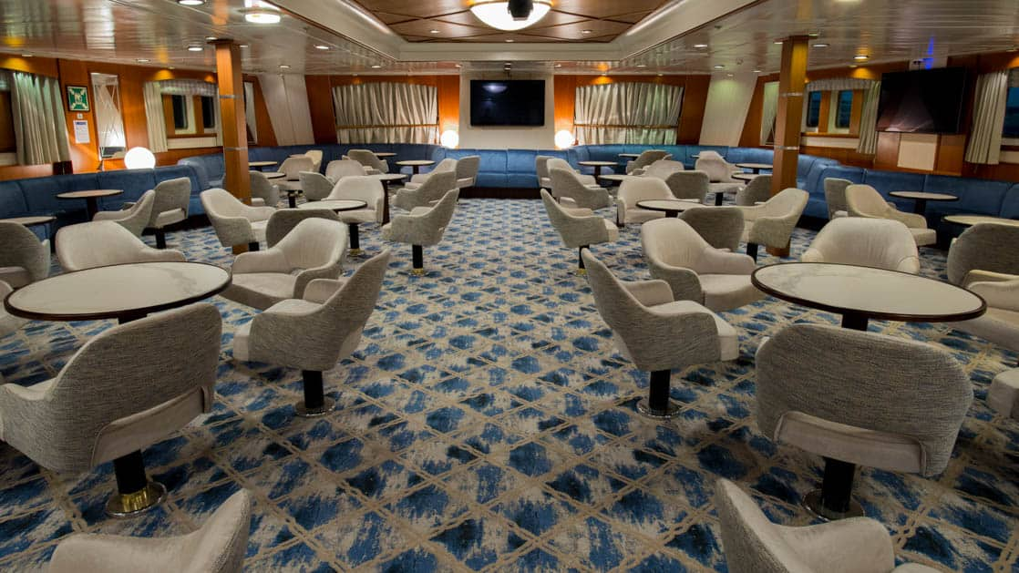 lounge area aboard Ocean Adventurer with groupings of tables and chairs