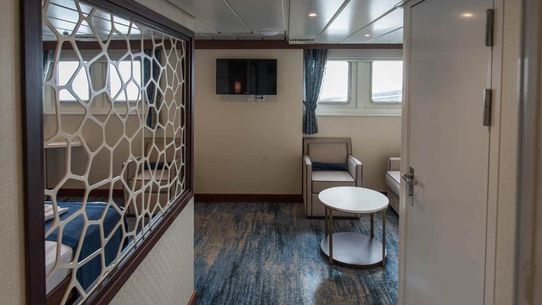 entrance of the owner suite aboard Ocean Adventurer with a mirror, stool and chairs