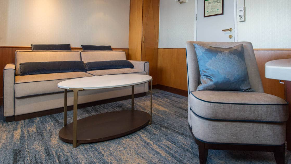 suite living room with a table, chair and couch aboard Ocean Adventurer