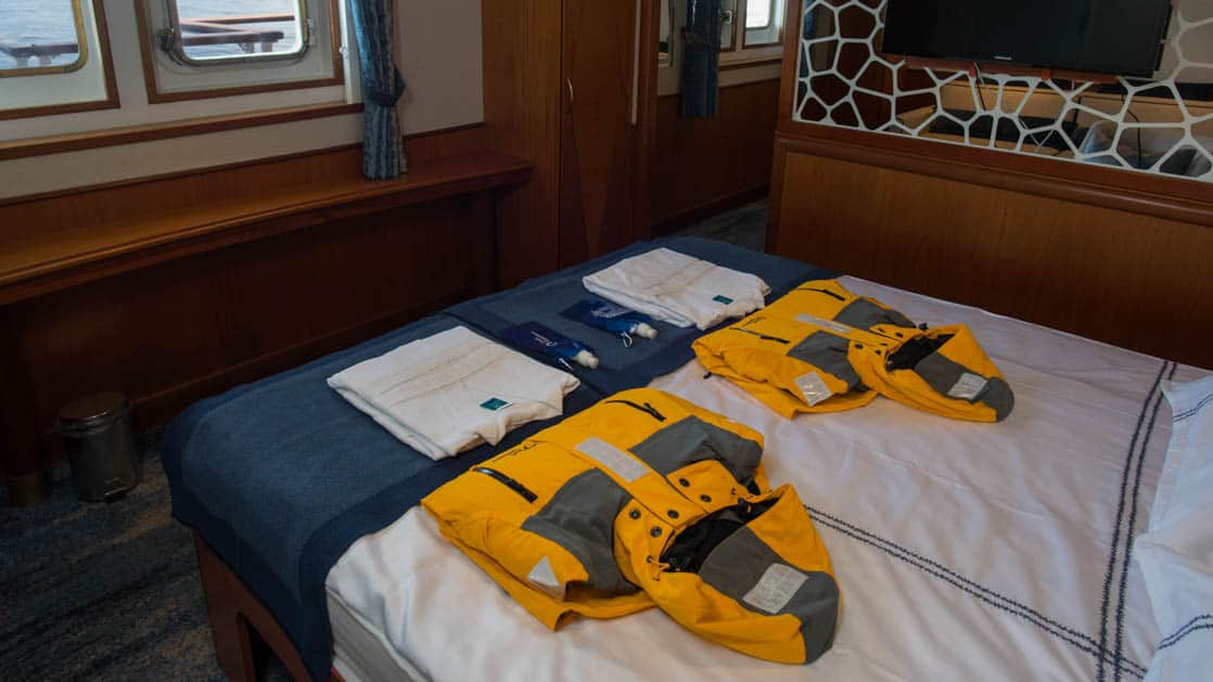 suite with large bed and jackets on the bed aboard Ocean Adventurer