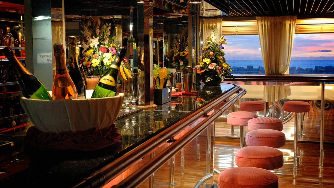 Wooden bar with red fabric barstools aboard Ocean Diamond polar ship, at sunset.