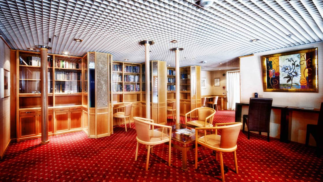 Library with red carpet, shelves of books & wooden tables & chairs aboard Ocean Diamond polar small ship.