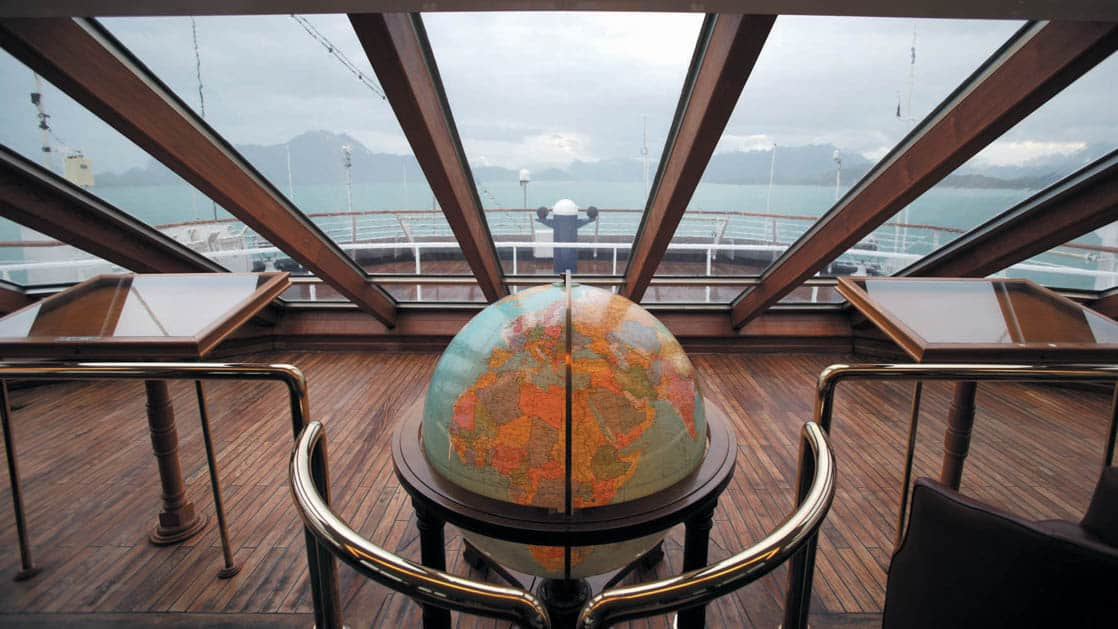 Observation lounge with large glass windows, wooden tables and a globe aboard Ocean Diamond polar small ship.