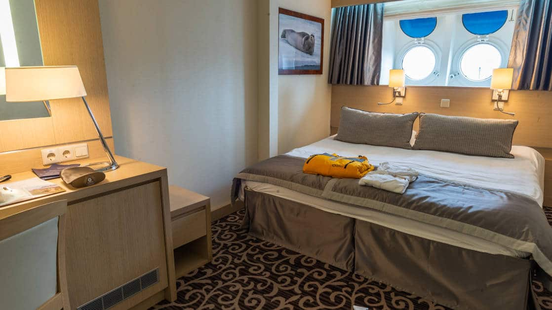 Large bed with side table and jacket set out for guest arrival and two porthole windows aboard the Ocean Diamond