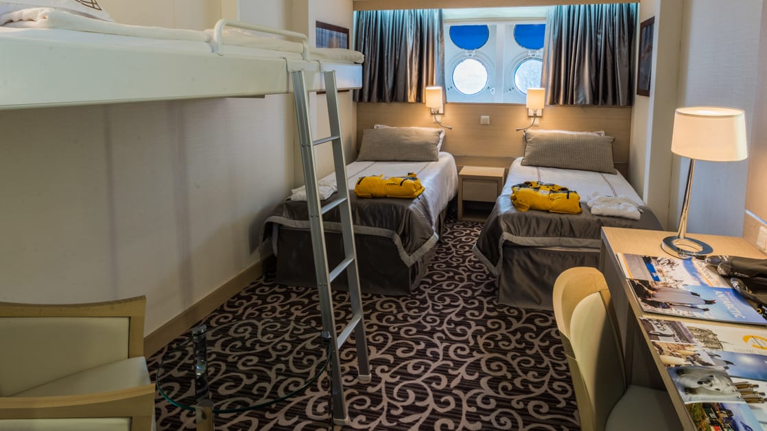 Triple cabin aboard Ocean Diamond polar expedition ship, with 3 twin beds, desk, couch & 2 portholes.