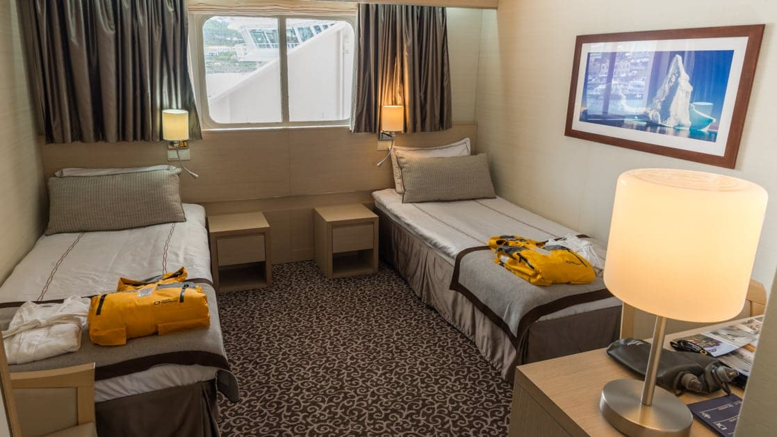 Two twin beds in a spacious room with window and side tables aboard the Ocean Diamond