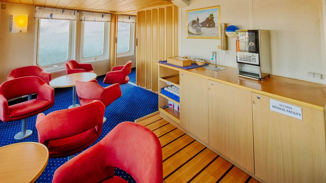 coffee station with red chairs and counter aboard the ocean nova quark ship