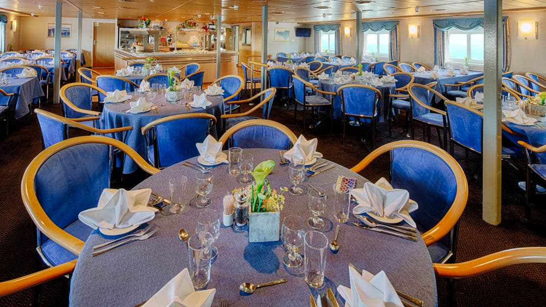 dining room full of tables and chairs inside the ocean nova quark small ship