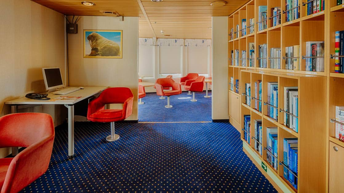 library with blue carpet and red chairs aboard the ocean nova quark small ship