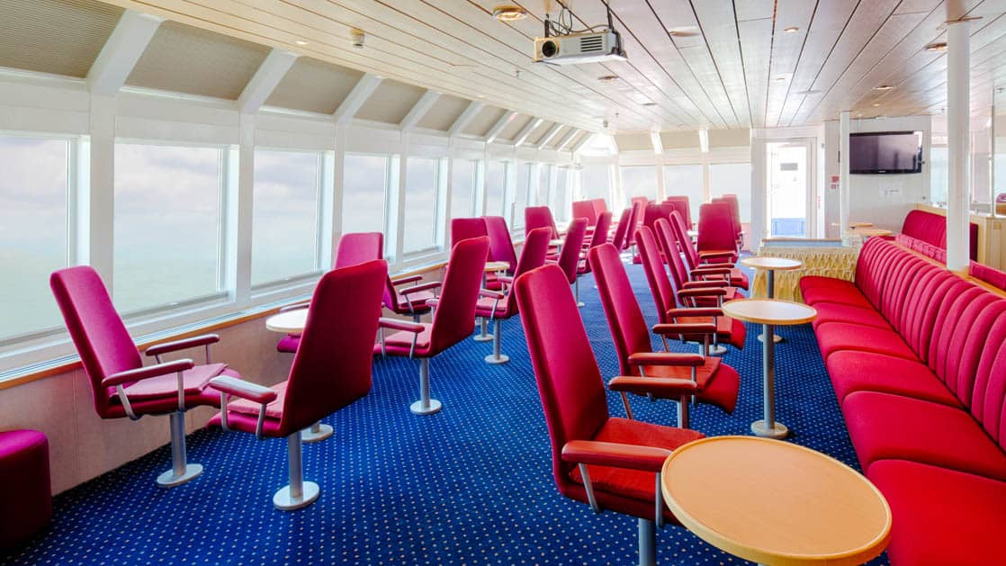 room with rows of red chairs and tables aboard the ocean nova quark