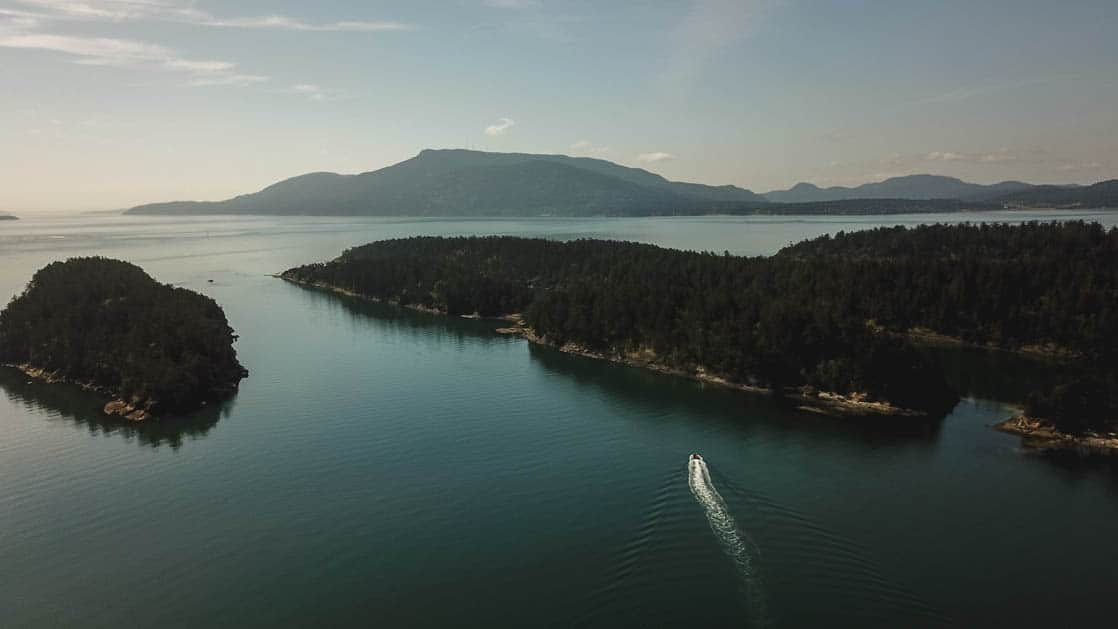 aerial view of sucia island in the pacific northwest while a small ship travels through a channel