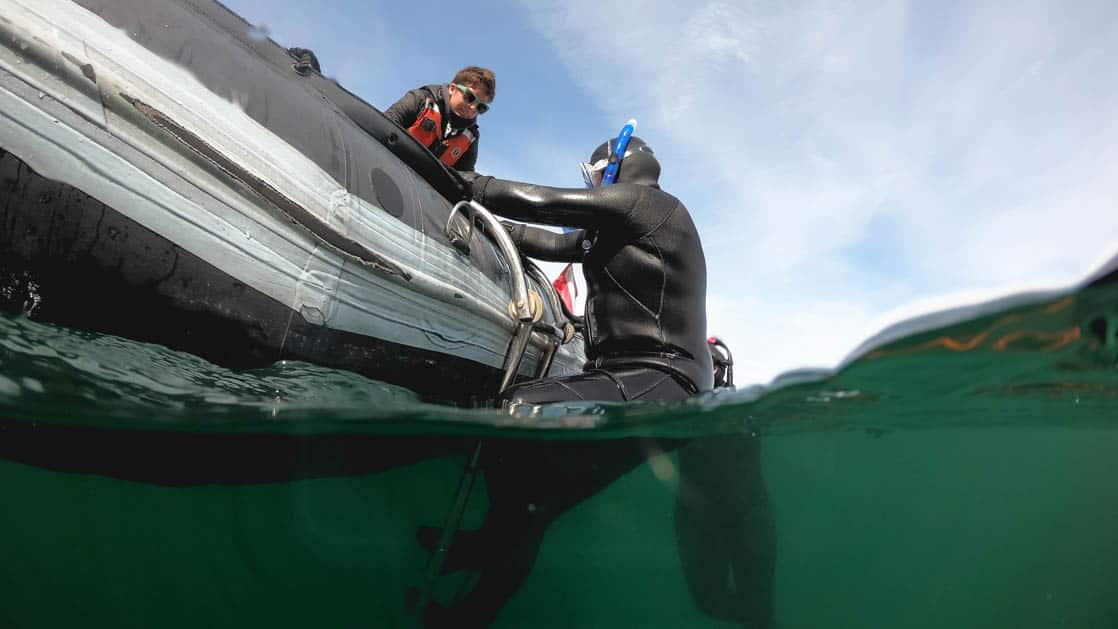 a guide helps an adventure traveler in a full body wetsuit enter the water from a skiff inflatable raft at one of the stops of the Olympic Wilderness & San Juan Islands small ship cruise
