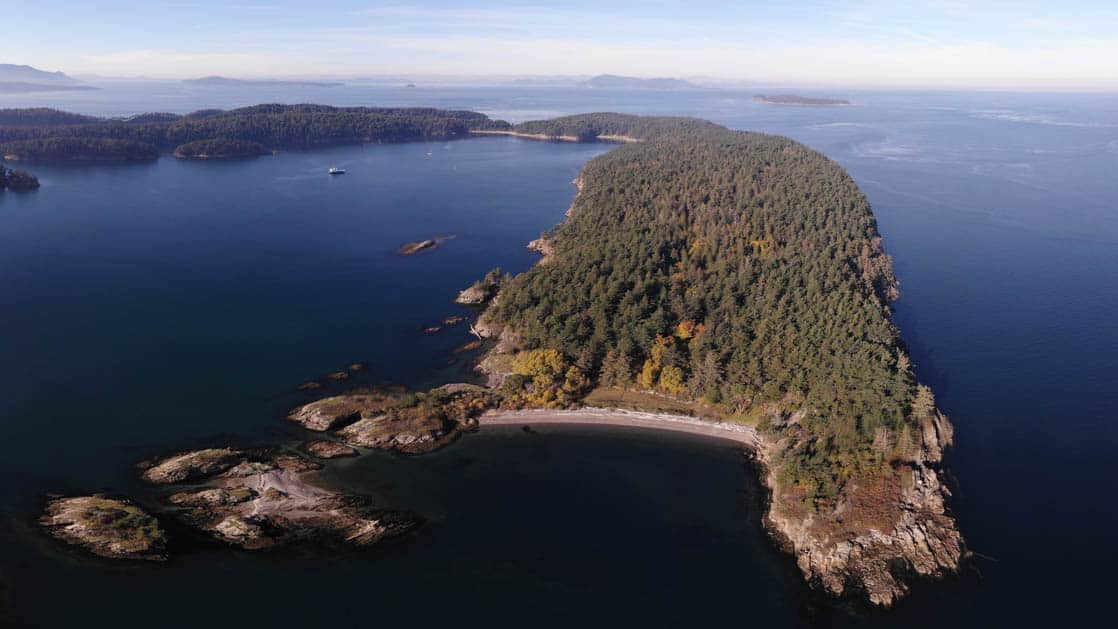 aerial view of sucia island in the pacific northwest on the Olympic Wilderness & San Juan Islands cruise with the safari quest small ship anchored in the distance