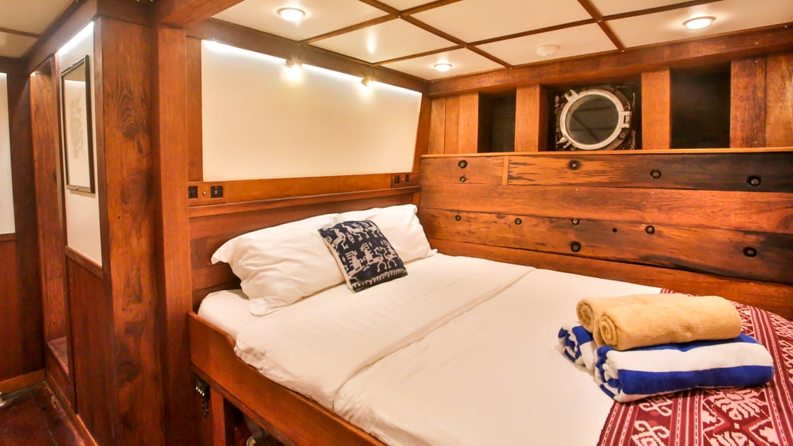 room with large bed and wooden walls aboard the ombak putih small ship