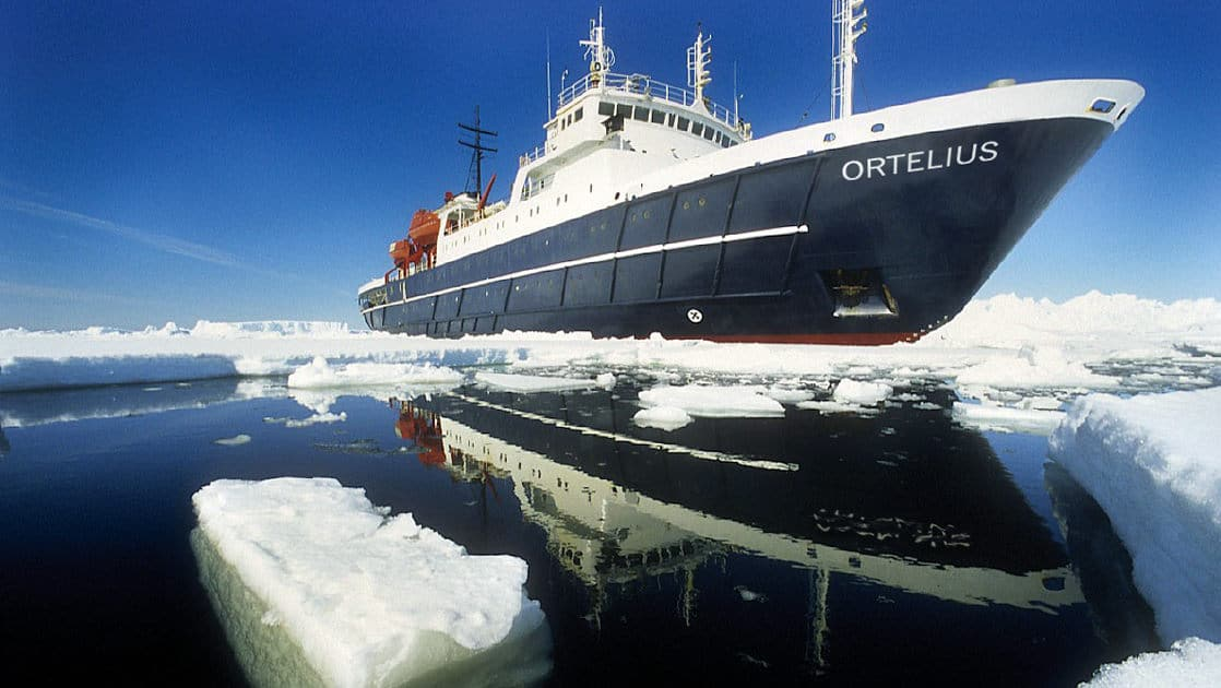 the ortelius small ship sailing on a sunny day with sea ice in the foreground