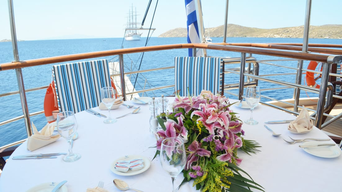 Out door dining area with set table aboard Callisto.
