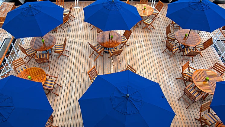 Outdoor cafe with wood furniture and blue unbrellas on the Corinthian small ship.