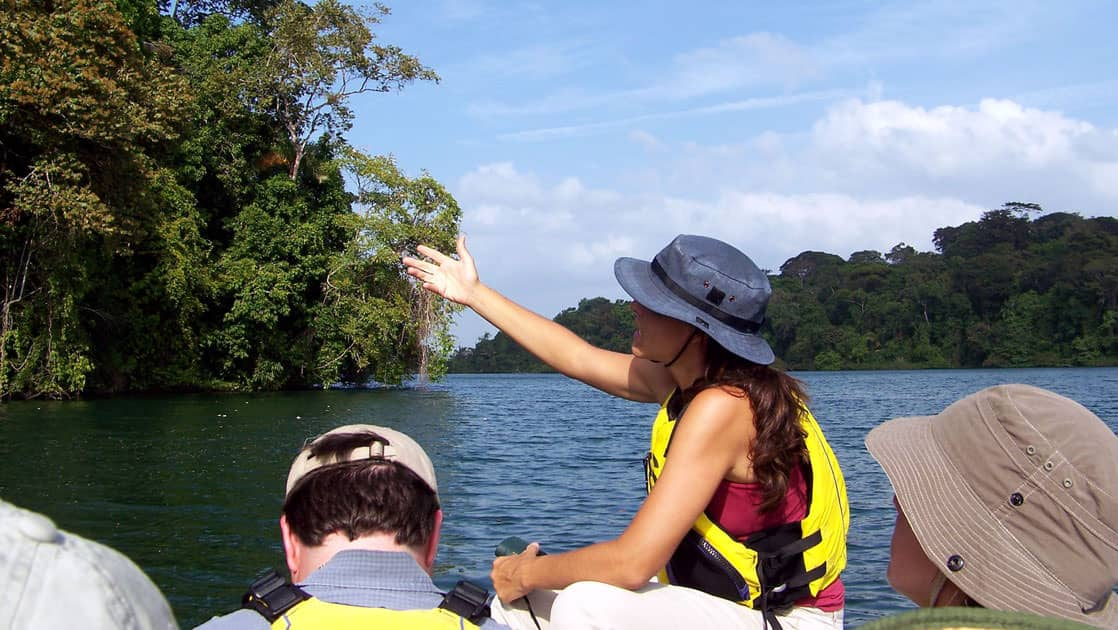 a guide on a skiff points to the jungle showing travelers something in the river during the Panama Adventure Cruise