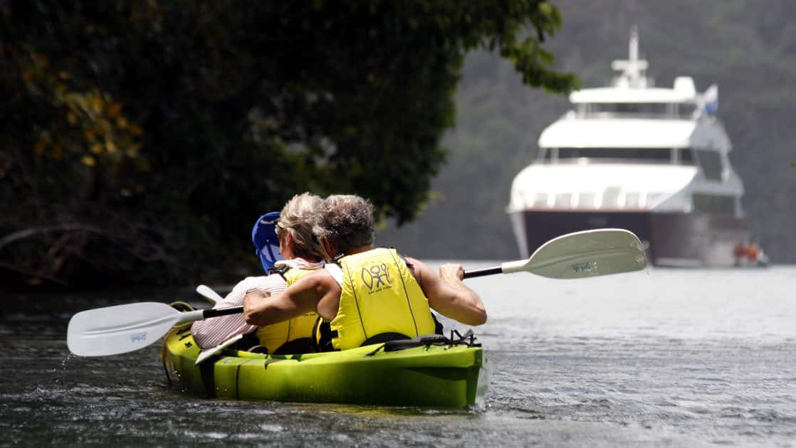 adventure travelers kayak next to the jungle while the Panama Discovery small ship sits anchored beyond them
