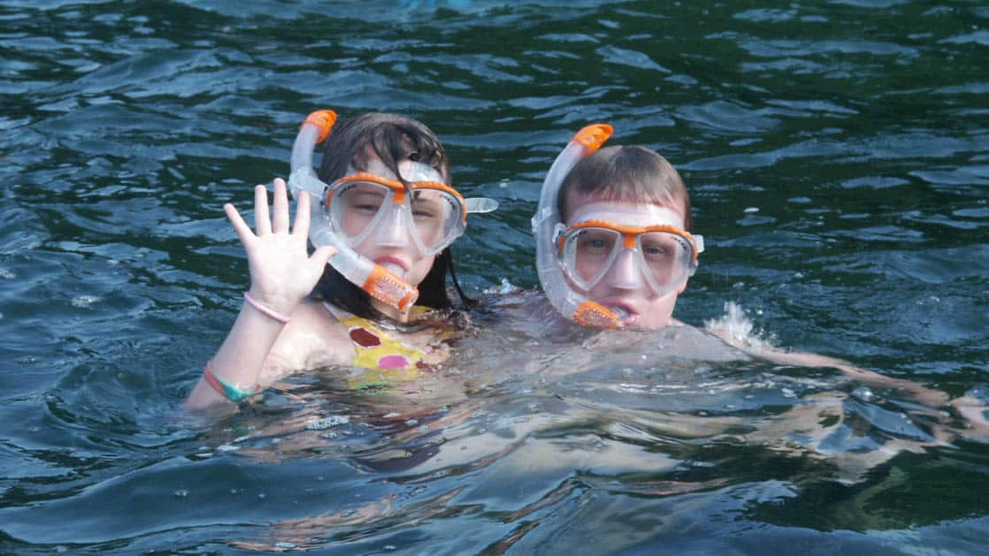 two kids with orange masks and snorkels wave from the water on the panama family adventure land tour