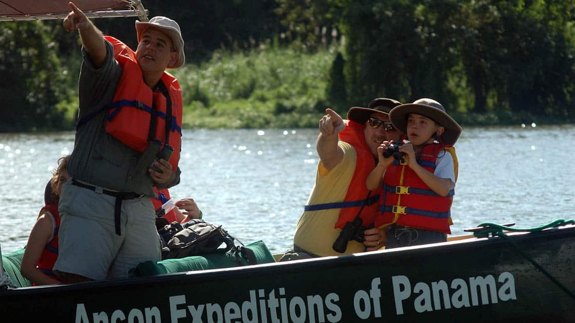 travelers point and take pictures during a jungle boat cruise on the panama family adventure land tour