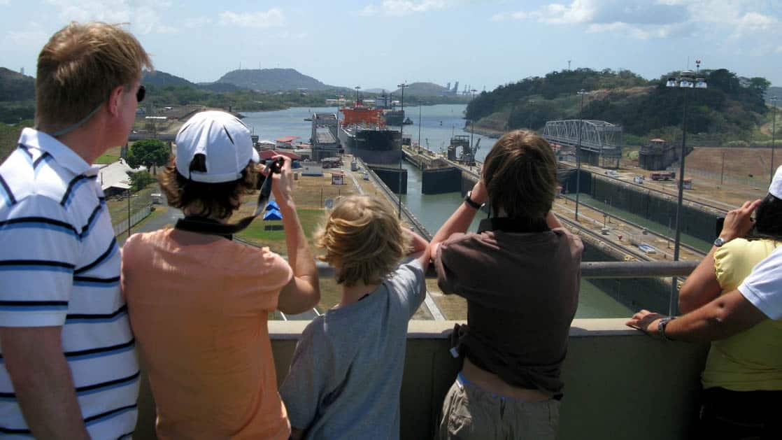 a family stands above the miraflores locks in panama on a sunny day pointing and taking pictures