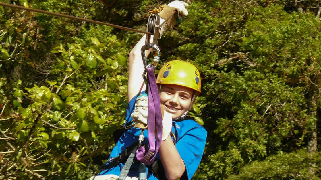 a teen with a yellow helmet ziplining in the jungle canopy on the panama family adventure land tour